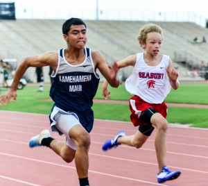 Kamehameha Maui's Tyler Baldonado-Kaleiopu and Seabury Hall's Noah Payne show their sprint technique midway through the first heat of the boys 100-meter dash. Baldonado-Kaleiopu was timed in 12.36 and Payne in 12.47. Photo by Rodney S. Yap.