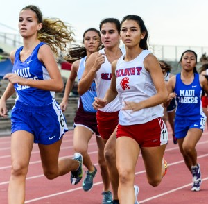 Seabury Hall's Veronica Winham and Sara Mutzenburg run to the inside of Maui High's Emily Craig (left) at the start of the girls 1500 Friday at the Yamamoto Track & Field Facility. Photo by Rodney S. Yap.