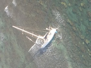 A 43-foot sailboat, Mithrandirs Dream, grounded approximately five miles east of Kaunakakai Harbor, Feb. 5, 2016. A Coast Guard MH-65 Dolphin helicopter crew from Air Station Barbers Point hoisted the two sailors aboard and safely transferred them to Kahului Airport, Maui. (U.S. Coast Guard photo courtesy of Air Station Barbers Point/Released)