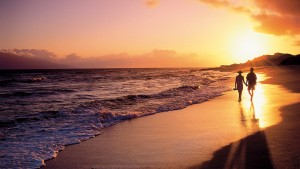 Couple on the beach at sunset.  Photo courtesy of Four Seasons Resort Lānaʻi.