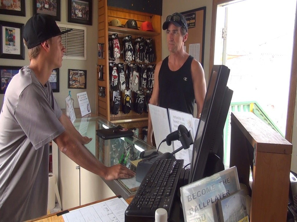 Hitter's Paradise employee Jack Klingman and customer Ty Roberts at the cash register, which the owner says was found on the ground after the theft. Photo by Kiaora Bohlool.