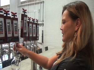 Christine Elumba works the taps at Koholā Brewery in Lahaina. Photo by Kiaora Bohlool.