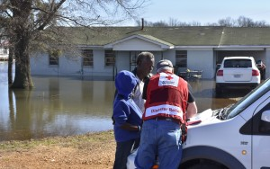 March 13, 2016. Robinsonville, Mississippi. American Red Cross client assistance teams canvassed areas of North Mississippi (Tunica County) that were affected by floodwaters. Paul Strickland and his son Paul Strickland, Jr. share their ordeal and complete paperwork with Red Cross caseworker Mike Peterson in front of his Robinsonville, Mississippi, home now surrounded by floodwaters. Photo by Bob Wallace/American Red Cross