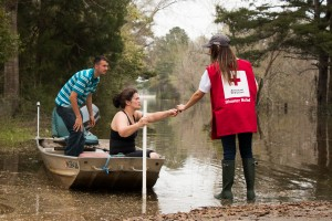 Wednesday March 16, 2016. McClain, Mississippi. Suzy Cooley and Aaron Cooley brave the flood waters on a fishing boat in McClain, MS. Red Cross volunteer, Sarah Basel, notifies them of a nearby Red Cross Point of Contact. Photo by Shannon Toombs/ American Red Cross