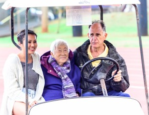 The wife, Doris, of the late Satoki Yamamoto and grand daughter Aleysa Martin get a ride from Maui Track & Field Officials Association President Allan Fernandez right before being introduced to the crowd at Saturday's finals of the 63rd MIL Yamamoto Invitational track meet. Photo by Rodney S. Yap.