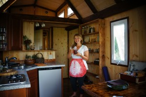Island Tiny Homes, Jen Chalupsky in the kitchen. Photo credit: Kailea Sonrisa, www.harnessyourbreath.com