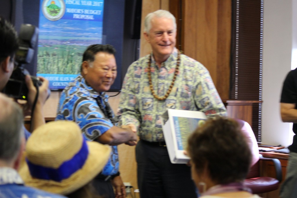 Maui Mayor Alan Arakawa (left) hands of the 920 page budget document to Maui Council Chair Mike White. Photo (3.24.16) by Wendy Osher.