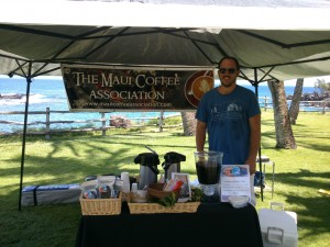 David Hanna at a booth at Montage in Kapalua, with a hand miller used to prepare coffee beans for winnowing and roasting. Courtesy of Maui Coffee Association.