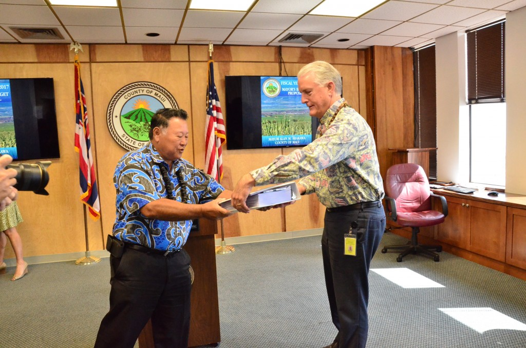 Maui Mayor Alan Arakawa (left) hands off his version of the Fiscal Year 2017 budget to Maui Council Chair Mike White (left). Photo credit: Maui Office of Council Services.