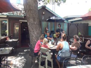 Diners enjoy live music on the outdoor patio at Three's Bar & Grill. Photo by Kiaora Bohlool.