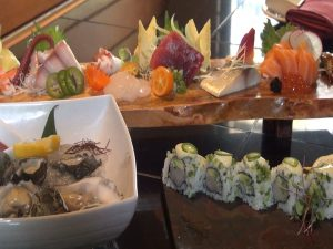 Sashimi platter, behind Kumumoto oysters and a jalapeño sushi roll. Photo by Kiaora Bohlool.