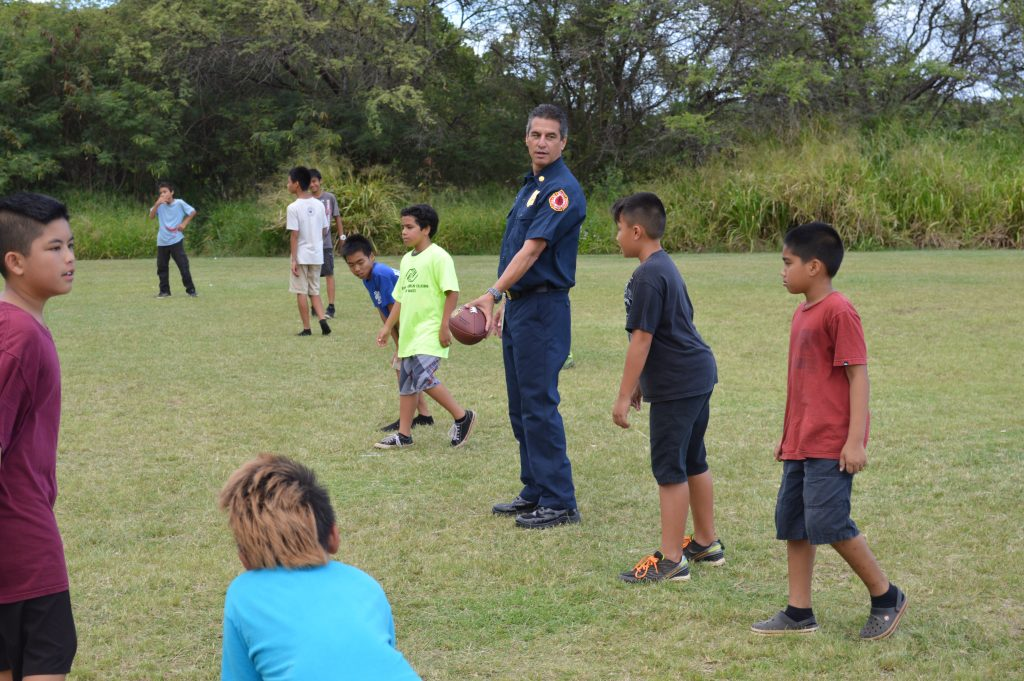 Maui Fire Chief Jeffrey Murray playing football with BGCM members. Photo credit: Boys & Girls Clubs of Maui.