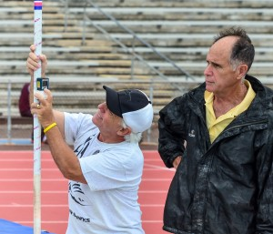 As head referee, Allan Fernandez signs off on all new records. Here he watches as pole vault official Gene Zarro measures the distance to the upright. Photo by Rodney S. Yap.