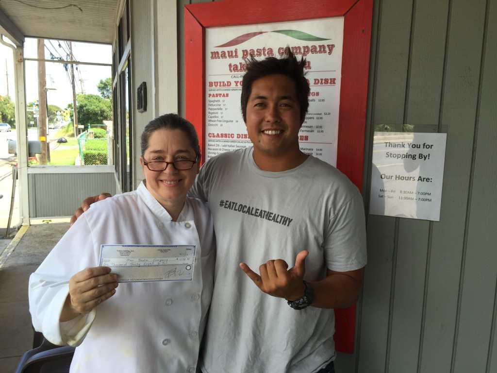 Travis Morrin Catering Director/Chef Co-Owner Three's Catering delivers a $1,038 check to Patricia Inman at Maui Pasta Co. as she faced unexpected financial hardship. Courtesy photo.