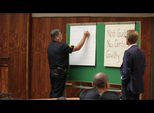 Defense attorney Samuel MacRoberts (right) asks Maui Police Sergeant Alan Brown (left) to draw a diagram of the Foodland parking lot where the police pursuit began.