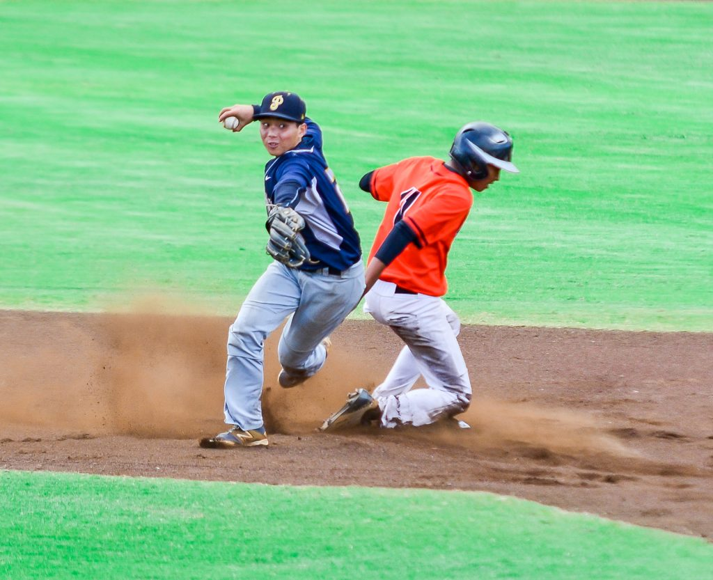 Punahou's Kekoa Vieira throws to first base for a double-play attempt after forcing out Campbell's Darien Robinson at second base. Photo by Rodney S. Yap.