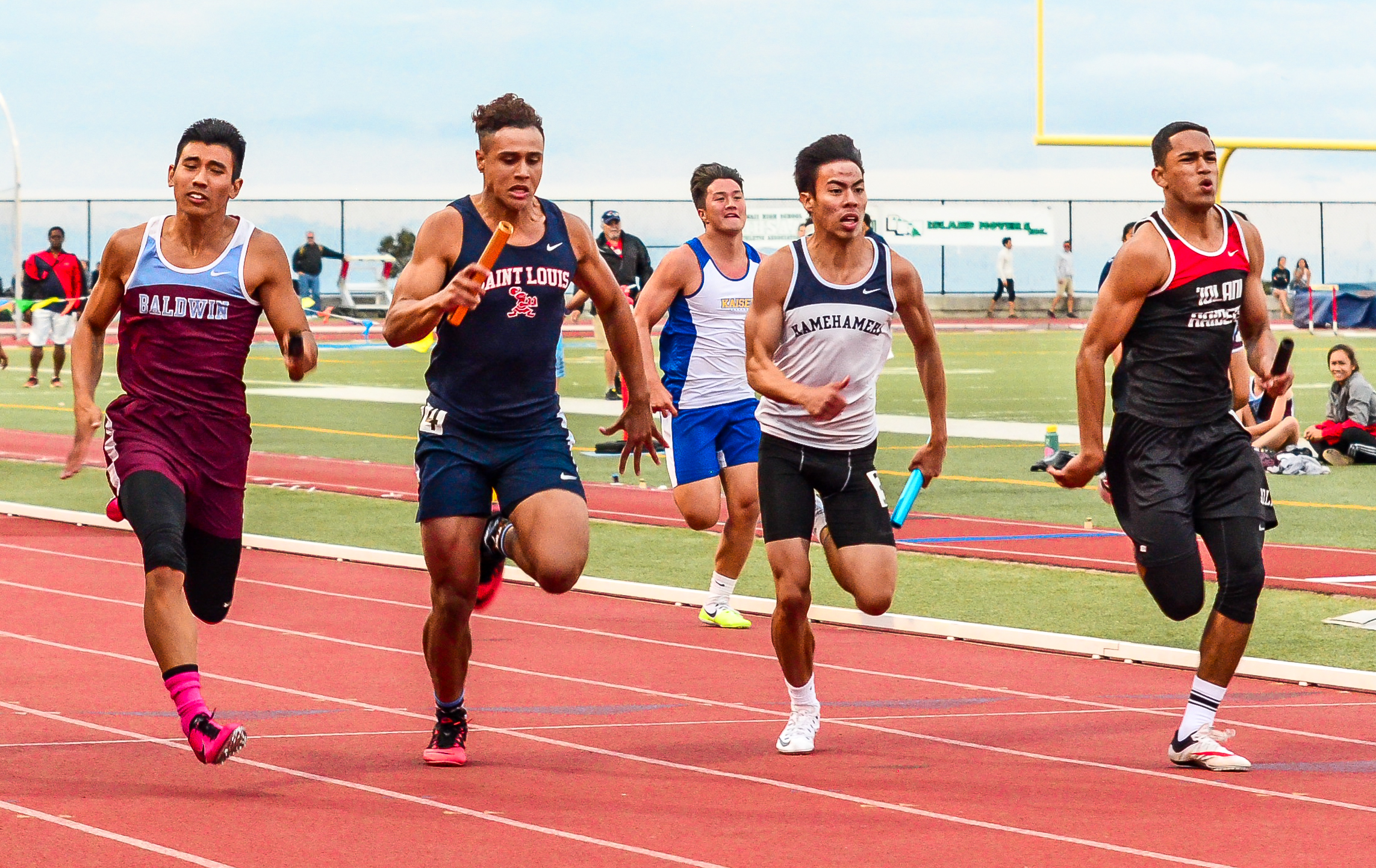 Baldwin's Baily Kaopuiki (left) edged out Saint Louis, Kamehameha Kapalama and Iolani to win the boys 4x100 relay last Saturday. Photo by Rodney S. Yap.