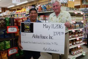 Pukalani Superette Owner Myles Nakashima presents acheck to Aloha House CEO Jud Cunningham.