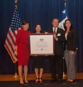 """US Secretary of Commerce Penny Pritzker (left) and US Rep.Tulsi Gabbard presented the Hawai'i Tourism Authority with the President's """"E"""" Award today in Washington, DC. Accepting the award was HTA President and CEO George D. Szigeti and HTA Director of Communications Charlene Chan.Photo credit: US Department of Commerce"""