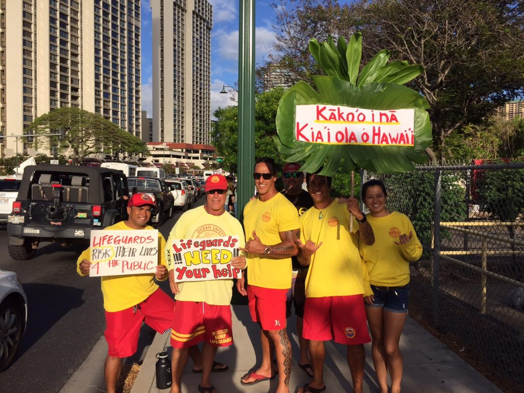 Hawaii Government Employees Association Unit 14 members (ocean/water safety and state law enforcement officers) and their supporters waved signs and rallied on Monday, May 9, along Ala Moana Blvd in a show of solidarity for their colleagues on Maui. The sign wavers are urging the Maui County Council to pass funding legislation for the Unit 14 arbitration decision that was finalized and awarded by an arbitration panel on February 22 of this year. Courtesy photo.