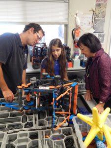 Maui Preparatory Academy instructor Branden Hazlet and student Violetta Thompson show Maui Electric President Sharon Suzuki a STEAM—STEM and Art—project.