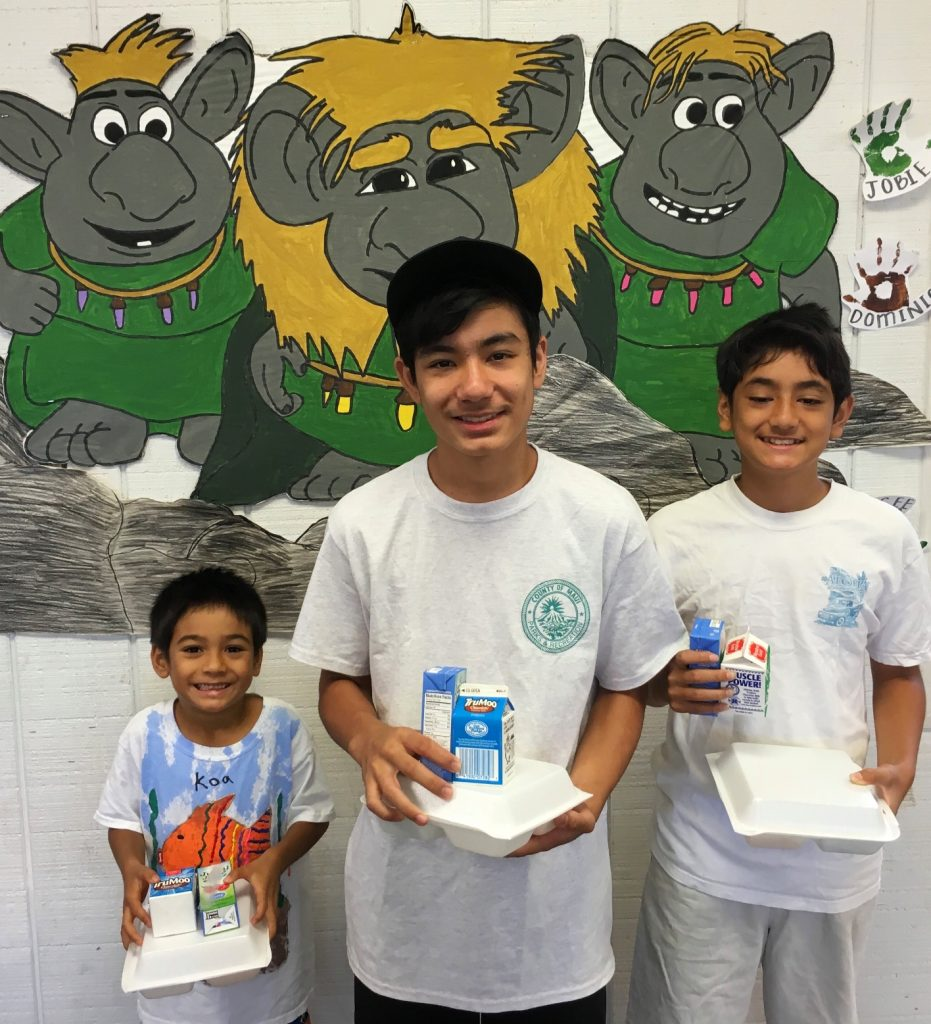 Three brothers from KCC PALS enjoy their meal: Koa (Kindergarten), Nalu (5th and Up) and Pono Akiona, a PALS volunteer. Photo credit: County of Maui, Dept. of Parks and Recreation (Ryan Min).