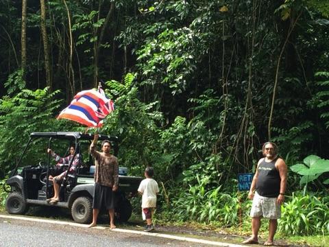 Lanakila Akuna with flag and kalo farmer Bush Martin. Photo credit: Claire Garrigue.