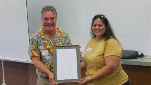 Outgoing NHOM President Dawn DeRego presented John Andersen, Na Hale O Maui's principal broker and former executive director, with a board resolution recognizing him as an instrumental founding NHOM member and for his years of dedicated service and commitment. NHOM photo.