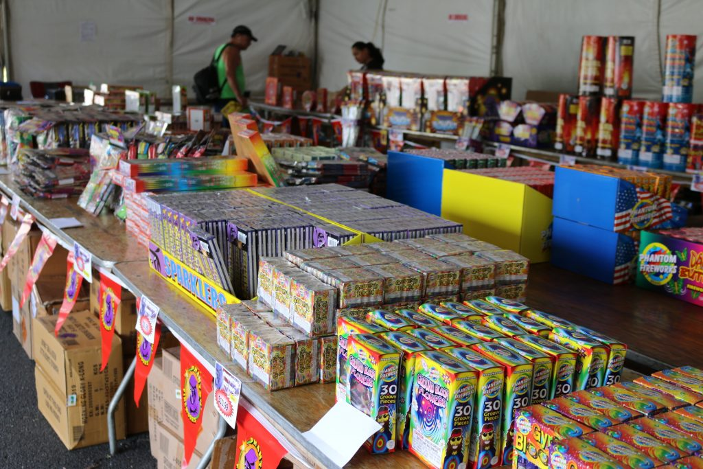 Customers looking at novelty fireworks at the Phantom Fireworks Tent at Queen Kaʻahumanu Center. Photo: Nicole Schenfeld