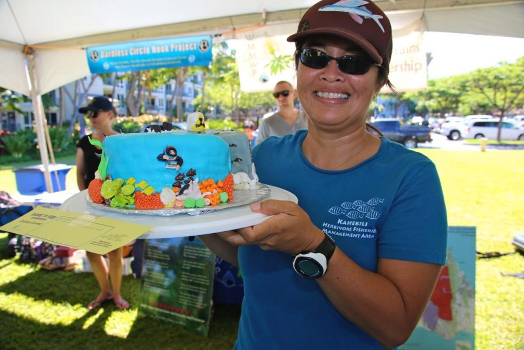 """Linda Castro with her 1st prize winning """"good reef/bad reef"""" cake in the Ridge to Reef Rendezvous' ocean-themed culinary contest in 2015. Photo credit: Terry Schroeder."""
