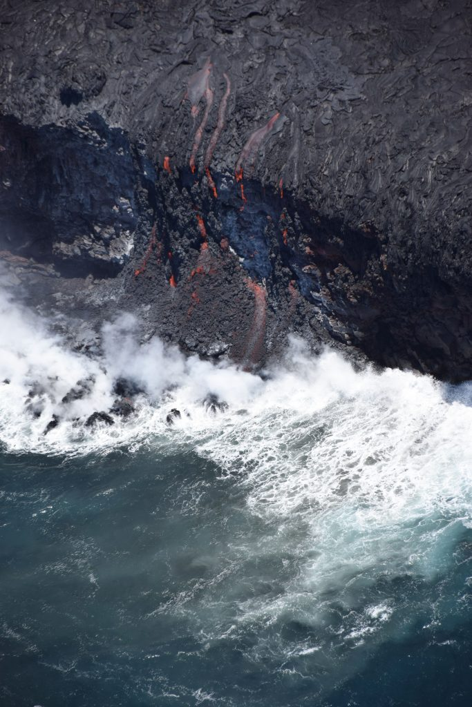 Less than 24 hours after first reaching the sea in the early morning hours of July 26, lava spilling over the sea cliff and into the ocean had started building a foundation of loose lava fragments on which a new lava delta can form. Lava deltas are extremely dangerous because they can collapse into the ocean without warning, triggering explosions that hurl rocks on and off shore, and sending waves of scalding water onto the coast. The area of active lava pouring over this sea cliff is about 20 m (66 ft) wide and the cliff is about 20 m (66 ft) high.  USGS photo.