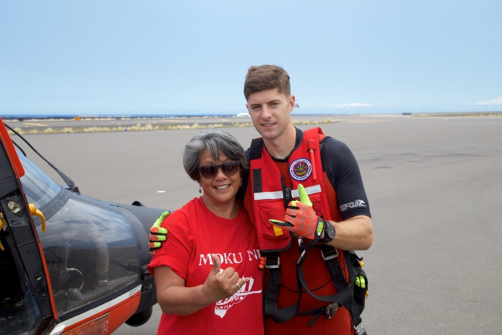A Coast Guard rescue swimmer involved in the rescue stands with the mother of Sidney Uemoto following her daughter's rescue nine miles off Kona, Hawaii, July 15, 2016. Uemoto and David McMahon were both rescued by a Coast Guard MH-65 Dolphin helicopter crew following an expansive joint search by Navy, Royal New Zealand air force, U.S. Air Force and Coast Guard crews. (U.S. Coast Guard photo by Lt. Cmdr. Kevin Cooper/Released)