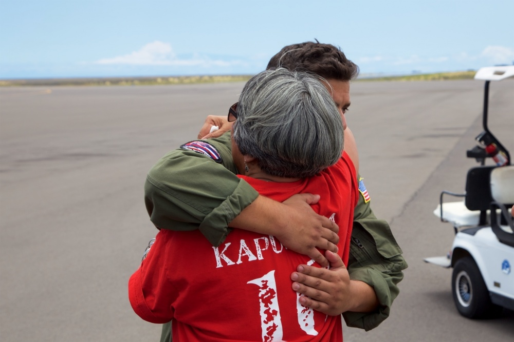 The mother of Sidney Uemoto hugs Coast Guard crews following her daughter's rescue nine miles off Kona, Hawaii, July 15, 2016. Uemoto and David McMahon were both rescued by a Coast Guard MH-65 Dolphin helicopter crew following an expansive joint search by Navy, Royal New Zealand air force, U.S. Air Force and Coast Guard crews. (U.S. Coast Guard photo by Lt. Cmdr. Kevin Cooper/Released)