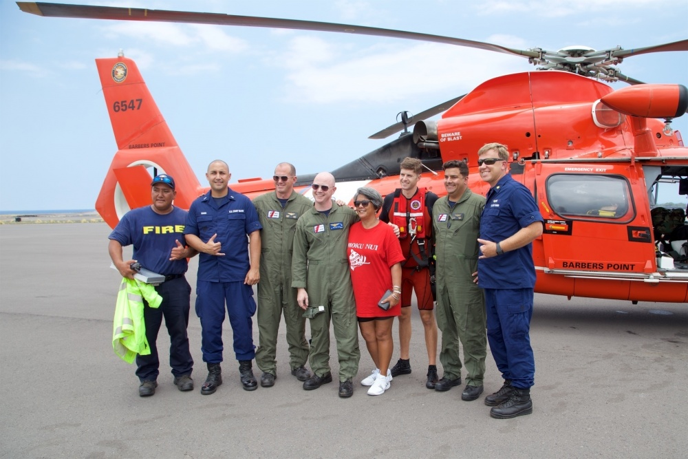 Coast Guard and Hawaii Fire Department personnel stand with the mother of Sidney Uemoto following her daughter's rescue nine miles off Kona, Hawaii, July 15, 2016. Uemoto and David McMahon were both rescued by a Coast Guard MH-65 Dolphin helicopter crew following an expansive joint search by Navy, Royal New Zealand air force, U.S. Air Force and Coast Guard crews. (U.S. Coast Guard photo/Released)