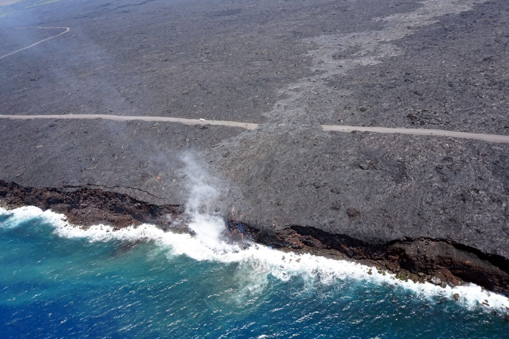 Just over two months since the start of the 61g flow, it reached the ocean on July 26 at 1:15 am HST. The narrow ocean entry was creating a small plume of gas and steam during today's overflight as the lava came into contact with the ocean. Photo credit: USGS/Hawaiian Volcano Observatory.