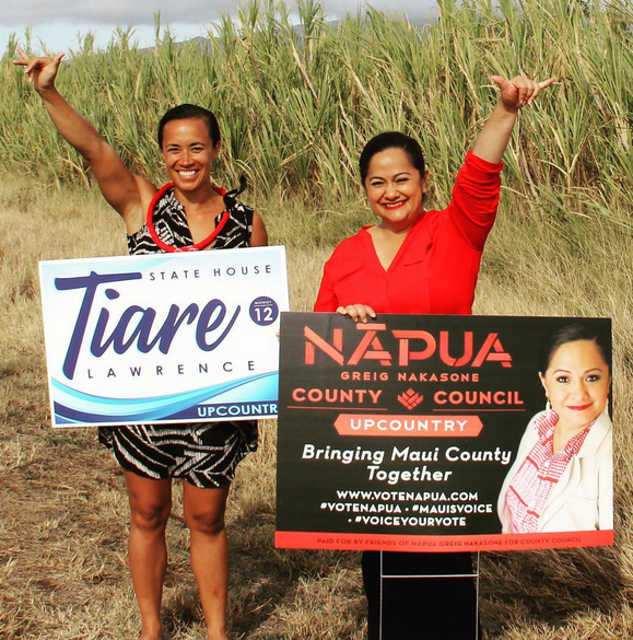 Aloha 'Aina candidates Tiare Lawrence (left) and Napua Greig-Nakasone sign wave on a Valley Isle roadside Tuesday, June 28. They seek to represent Upcountry in the Hawai'i state House and Maui County Council, respectively, and will appear at a candidates forum 6 p.m. Thursday, July 7, at Keokea Marketplace. Photo credit: Votetiare.com image votetiarte.com