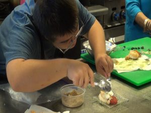Easter Seals participant helps prepare appetizer. Photo by Kiaora Bohlool.