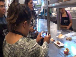 Easter Seals participant documents the action in the kitchen at Sugar Beach Events. Photo by Kiaora Bohlool.