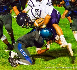 King Kekaulike's Kele Pacheco (1) tries totake down Kamehameha Maui running back Damon Martin during Thursday night's action King Kekaulike Stadium. Pgoto by Rodney S. Yap.