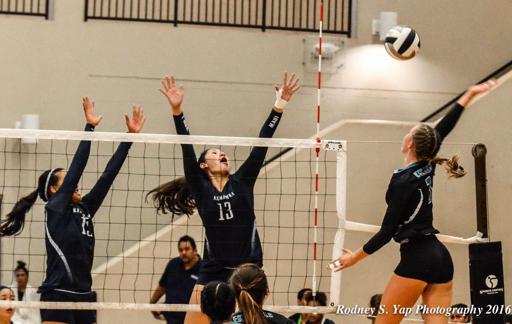 King Kekaulike junior outside hitter Chandler Cowell goes above the block of Kamehameha Maui's Kylee Yamamshita (13) and Caylee Tuzon (15). Photo by Rodney S. Yap.