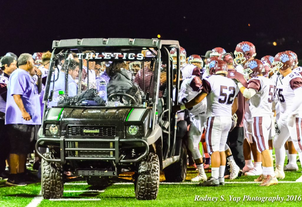 Baldwin players and coaches huddle around injured teammate Nainoa Keahi before he is carted off the field Saturday. Photo by Rodney S. Yap.