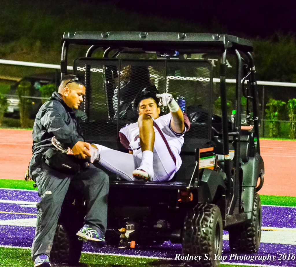 Baldwin linebacker Nainoa Keahi assures his teammates he will be fine one last time as he is carted off the field with school athletic trainer Scott Pagdilao assisting. Photo by Rodney S. Yap.