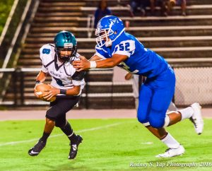 Maui High defensive end Jamie Fisher is about to sack King Kekaulike quarterback Earl Naki-Vea, during first-half action Friday at War Memorial Stadium. Photo by Rodney S. Yap.
