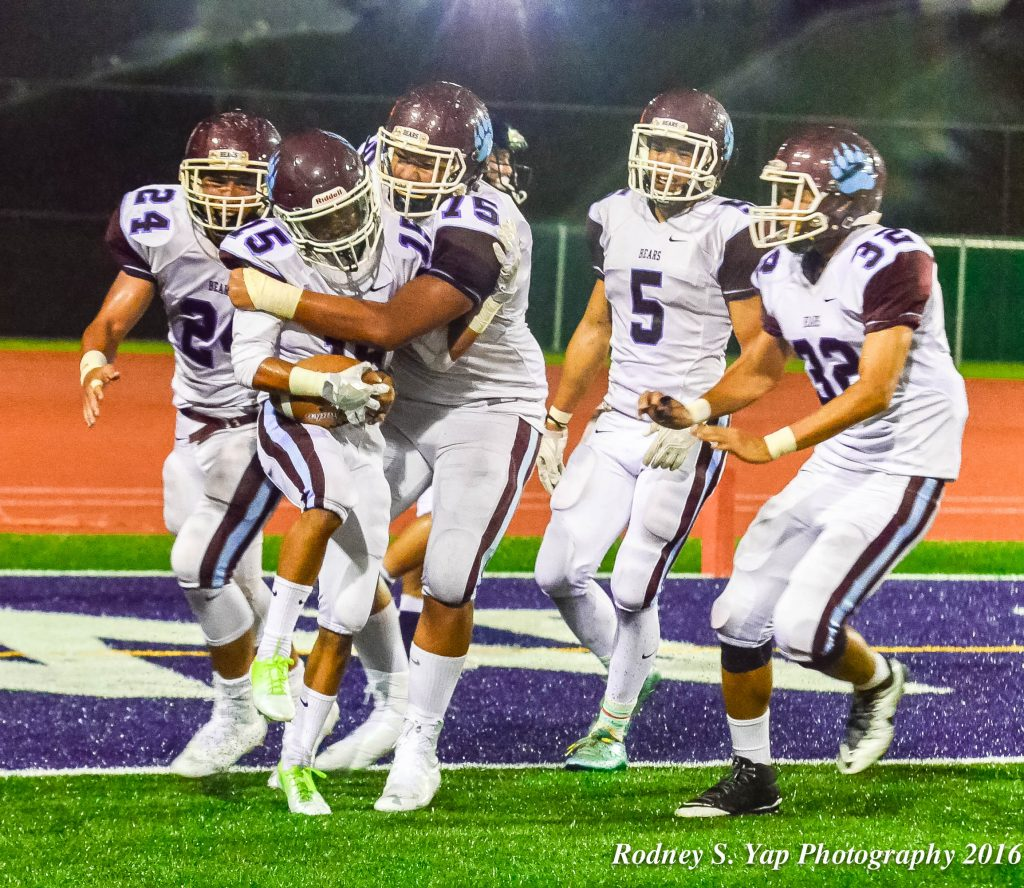 Baldwin's Dalton Mata (15) celebrates with teammates, including Gavin Arista (75), after hauling in for a 36-yard scoring toss with 36 seconds left before halftime. Photo by Rodney S. Yap.