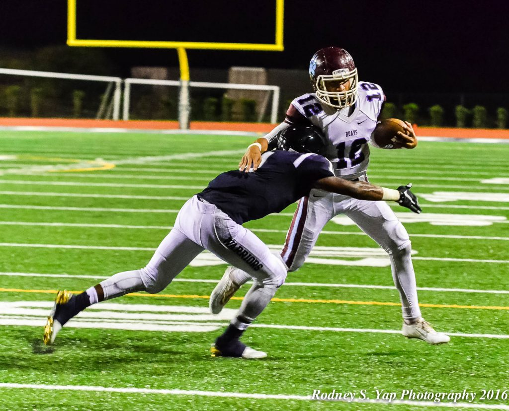 Baldwin's Chayce Akaka is forced out of bounds by a Kamehameha Maui defender after scrambling in the backfield. Photo by Rodney S. Yap.