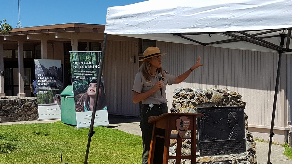 Superintendent Natalie Gates asks visitors to share their favorite park memories. She is standing next to a plaque honoring Stephen Mather, the first National Park Service Director.
