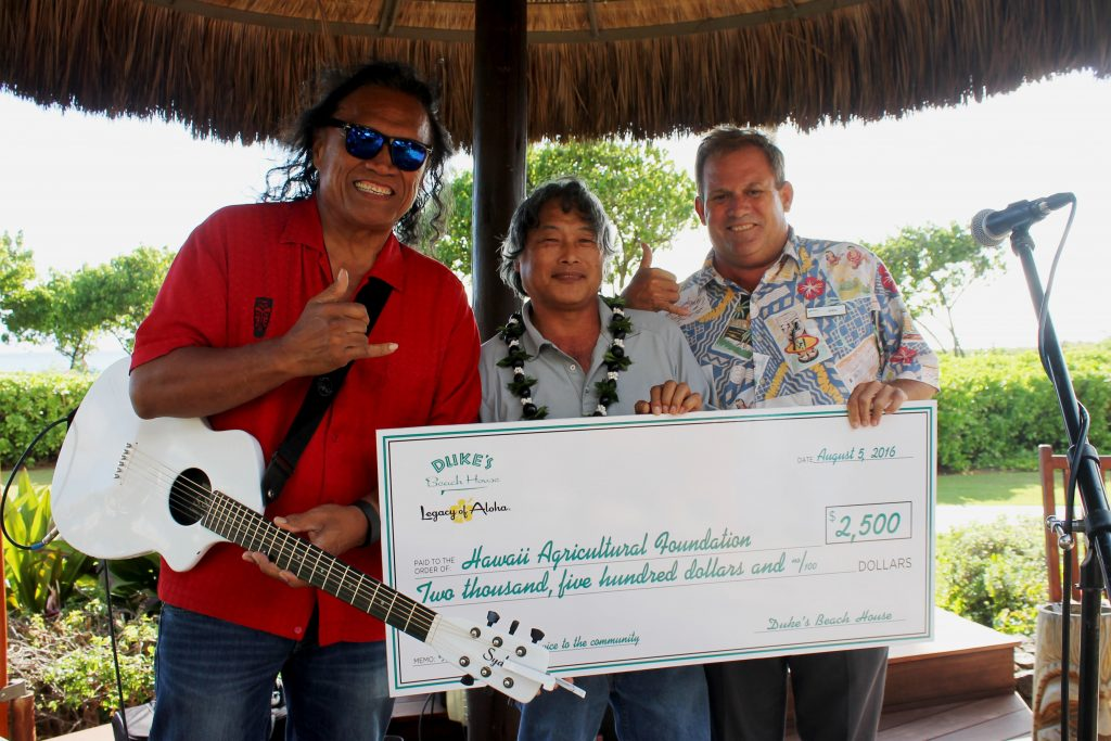 Duke's Beach House presented the Hawai'i Agricultural Foundation with a $2,500 check at the Henry Kapono performance. Pictured left to right: Henry Kapono, Warren Watanabe, Hawai'i Agricultural Foundation; John Brans, Duke's Beach House Manager. Photo Courtesy.
