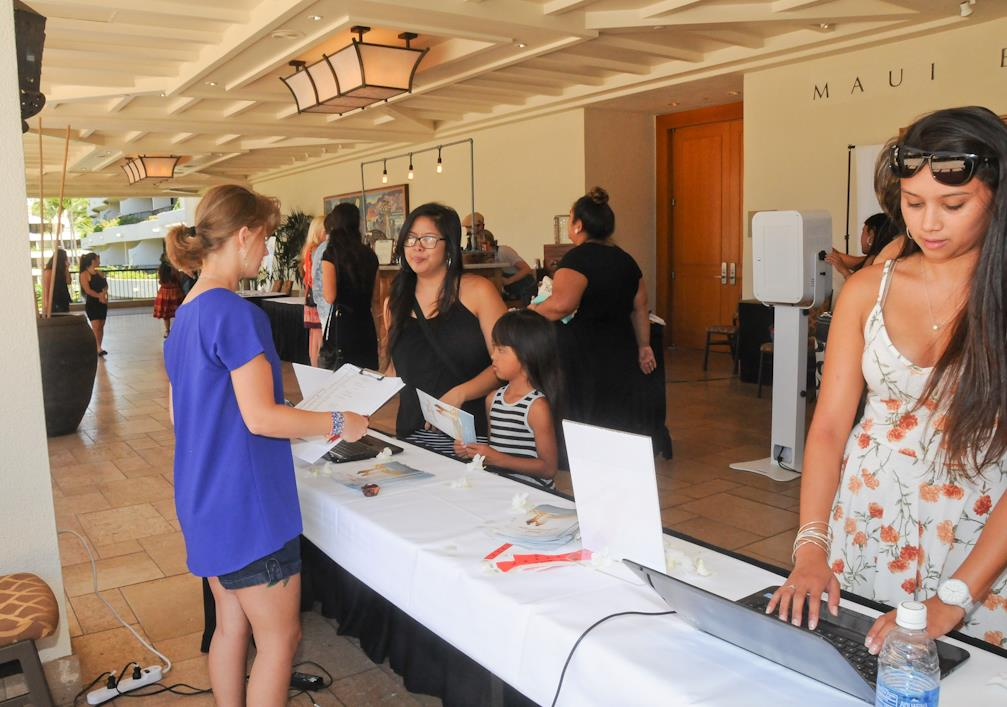 Elizabeth Clark checks in brides to be at the registration desk of the Maui Wedding Association's 21st Annual Maui Wedding Expo.