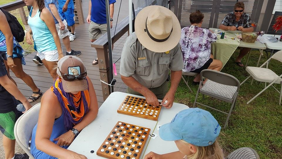 Ranger Walter shows visitors how to play konane. Photo courtesy Haleakalā National Park.