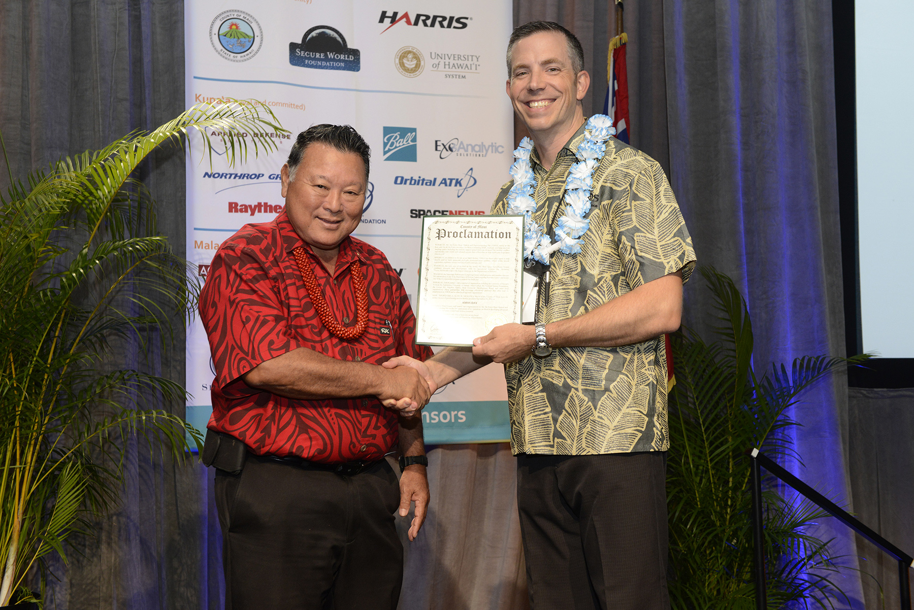 Mayor Alan Arakawa and Lieutenant Colonel Andrew Emery commander of Air Force Research Laboratory's Detachment 15 in Kihei, with a proclamation naming September 21 as AMOS Day.